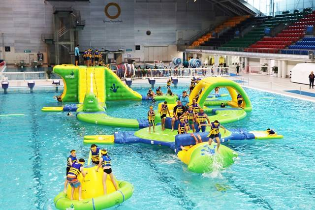 Kids playing on inflatable obstacle course in pool at Sydney Olympic Park Aquatic Centre